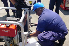 Coast Guard member attaching hydraulic lines to Fast Sweep Boom Prime Mover