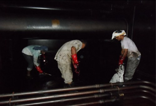 Men cleaning cargo tank.